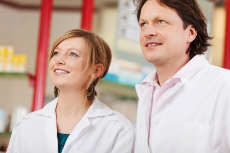 two confident pharmacists looking up photo