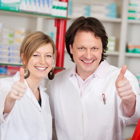 Portrait of confident pharmacists showing thumbsup sign in pharmacy photo