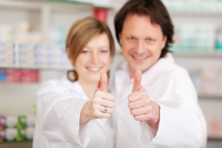 two smiling pharmacists showing thumbs up sign photo