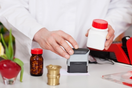 Midsection of male pharmacist stamping bill at pharmacy desk Stock Photo - 21165242