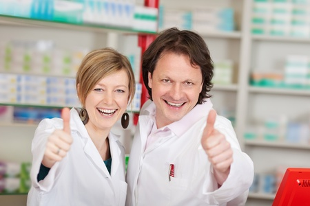 Portrait of happy pharmacists showing thumbsup sign in pharmacy Stock Photo - 21165235