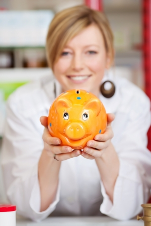smiling female pharmacist with piggy bank photo
