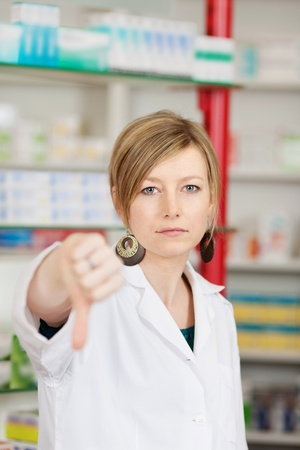 Portrait of young female pharmacist showing thumbs down sign photo