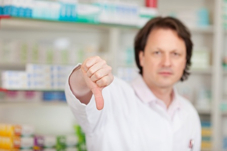 erious male pharmacist showing thumbs down photo