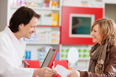 drug store: Happy pharmacist receiving prescription paper from customer in pharmacy Stock Photo