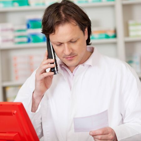 male pharmacist with prescription looking serious while on call photo