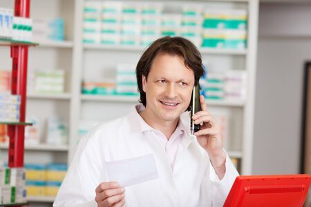 male pharmacist on call in a pharmacy with prescription photo