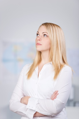 Close-up of a young blond businesswoman looking up in office photo