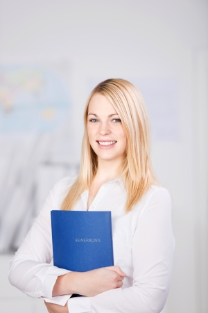 looking for a job: Portrait of young businesswoman holding application book while standing in office Stock Photo