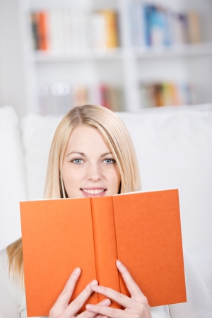 woman reading book: Portrait of beautiful young woman holding book in living room