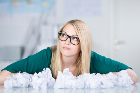 Thoughtful young businesswoman with paper balls on desk looking away in office photo