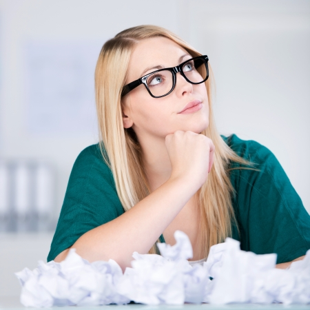 Thoughtful young businesswoman with paper balls on desk with hand on chin photo