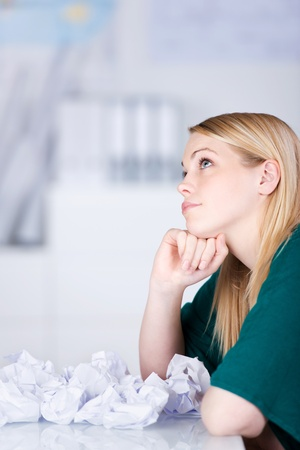 paperball: Thoughtful businesswoman with paper balls on desk looking away in office