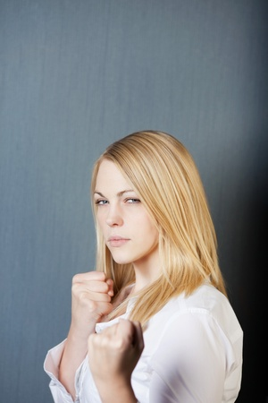 Portrait of an angry woman with clenched fists isolated over blue background