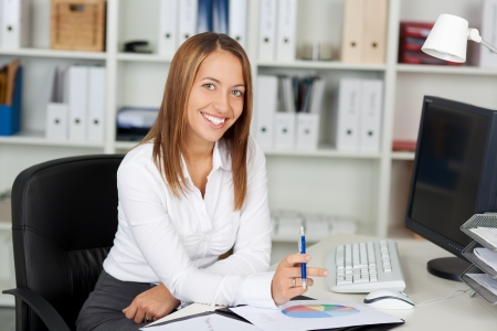 Portrait of happy businesswoman holding pen at office desk Stock Photo - 21167368
