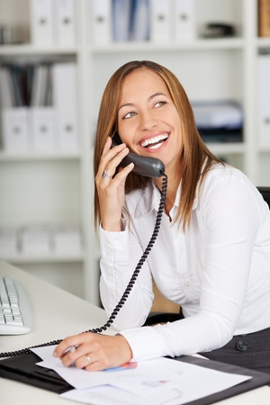 Happy young businesswoman using land line phone at office desk Stock Photo - 21167370