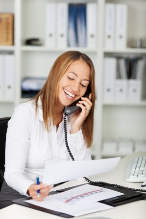 Happy young businesswoman using landline phone while holding paper at office desk Stock Photo - 21167371