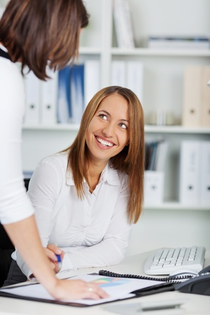 Portrait of young businesswoman explaining coworker at office desk photo