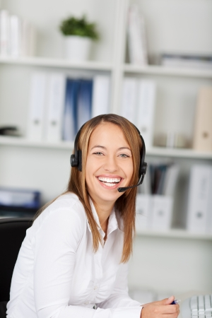 Portrait of laughing female customer service executive sitting at office desk photo