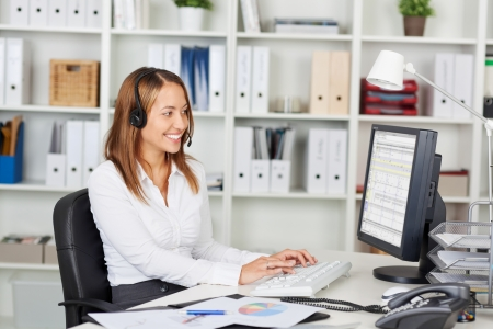 telephone headsets: Happy young businesswoman wearing headset while using computer at office desk