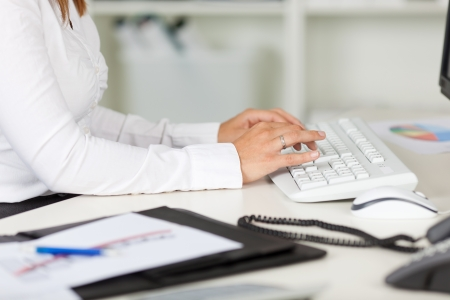 Cropped image of businesswoman typing on keyboard at office desk photo