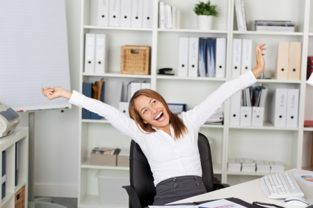arms open: Excited young businesswoman with arms raised sitting on chair at office desk