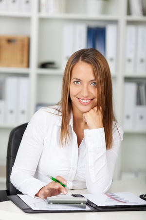 Portrait of confident businesswoman with hand on chin using calculator at office desk photo