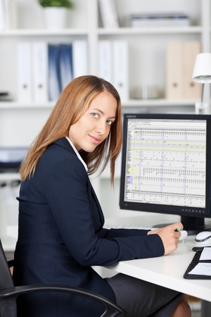 Portrait of confident businesswoman with computer on desk Stock Photo - 21167418
