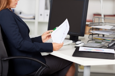 Midsection of businesswoman holding graph paper at office desk Stock Photo - 21167420