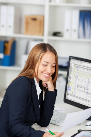 Happy young businesswoman with hand on chin looking at document in office Stock Photo - 21167421