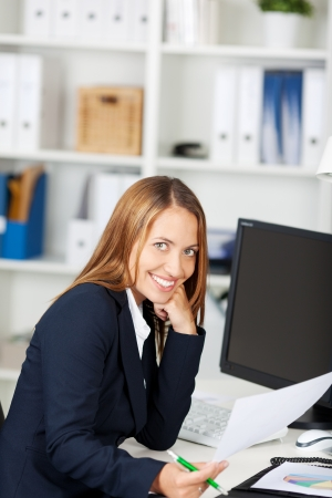 Happy young businesswoman with hand on chin looking at document in office Stock Photo - 21167422