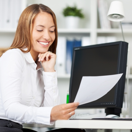 Happy young businesswoman with hand on chin looking at document in office Stock Photo - 21167423