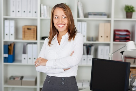 front office: Happy businesswoman with arms crossed looking away while standing in office