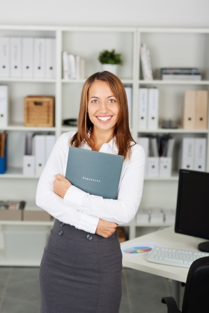 looking for a job: Young businesswoman with a curriculum vitae in her arms, looking for a job