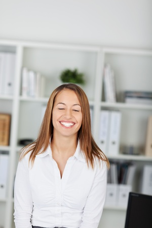 one eye closed: Happy young businesswoman with eyes closed standing in office Stock Photo