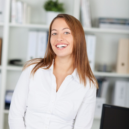 waistup: Modern young businesswoman in office smiling happily