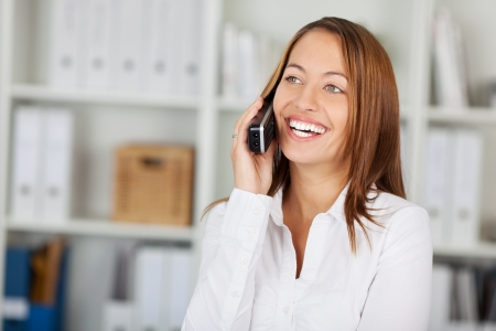 cordless: Happy businesswoman using cordless phone while looking away in office Stock Photo