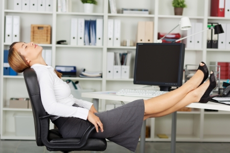 Happy businesswoman with eyes closed relaxing on office chair photo