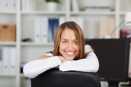 Portrait of happy young businesswoman leaning on chair in office Stock Photo - 21167457