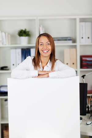 front office: Portrait of happy businesswoman leaning on blank billboard in office