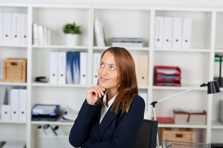 Thoughtful young businesswoman with hand on chin looking up in office Stock Photo