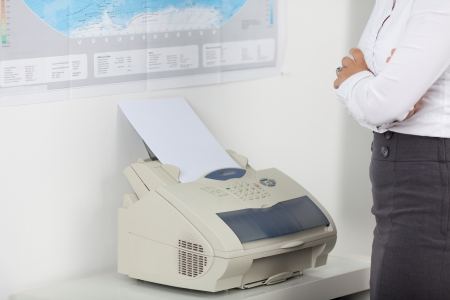 copy machine: Midsection of businesswoman using fax machine in office