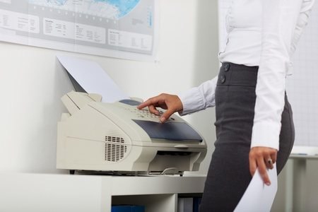Midsection of businesswoman using copy machine in office photo