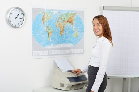 photocopier: Portrait of happy businesswoman using copy machine in office Stock Photo
