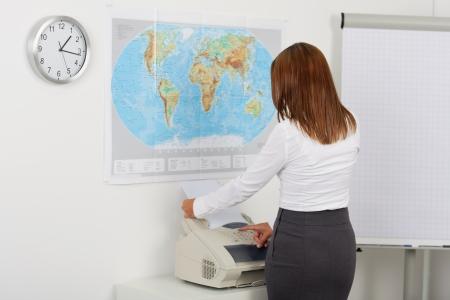 Portrait eines glücklichen Geschäftsfrau mit Faxgerät im Büro