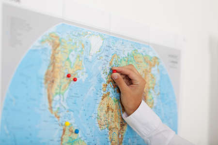 attaching: Closeup of businesswomans hand attaching pushpin on map in office