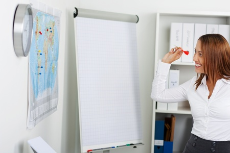 Happy young businesswoman throwing dart on world map at office photo