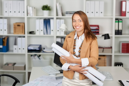 Portrait of happy businesswoman holding blueprints at office desk photo