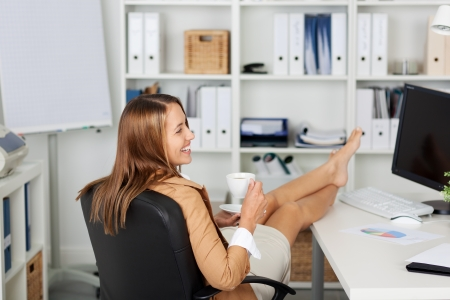 Rear view of young businesswoman having coffee at office desk
