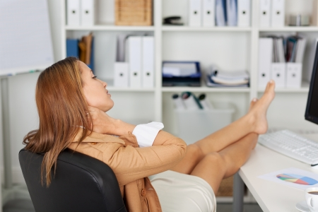 Relaxed young businesswoman suffering from neck pain while sitting on office chair at desk photo